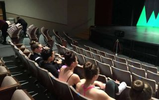 High school dance students watching recital rehearsal