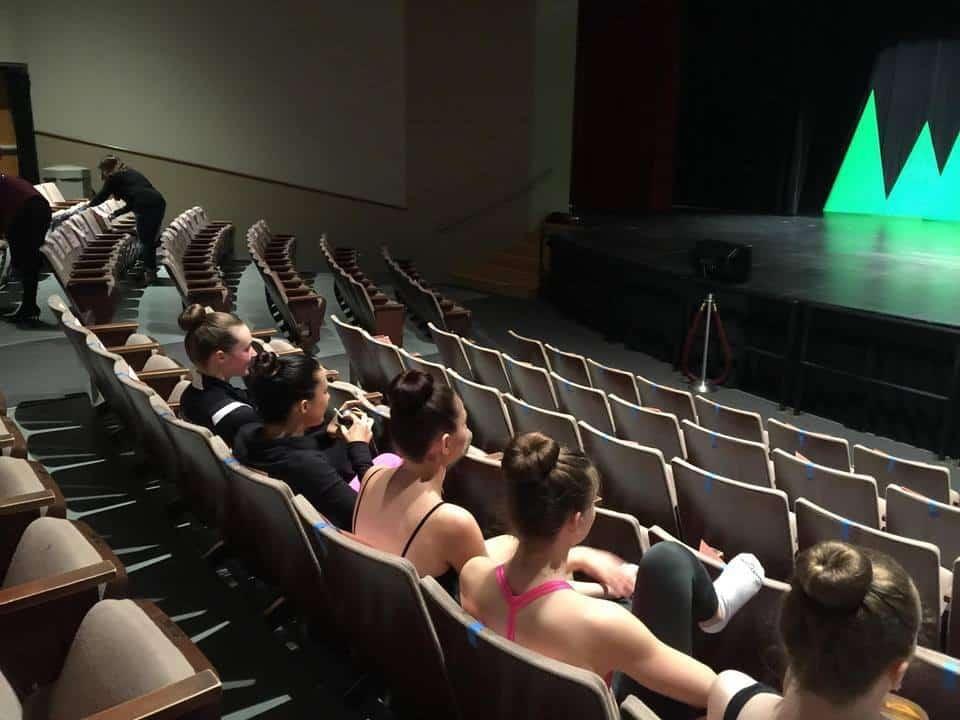 High school dance students watching recital rehearsal